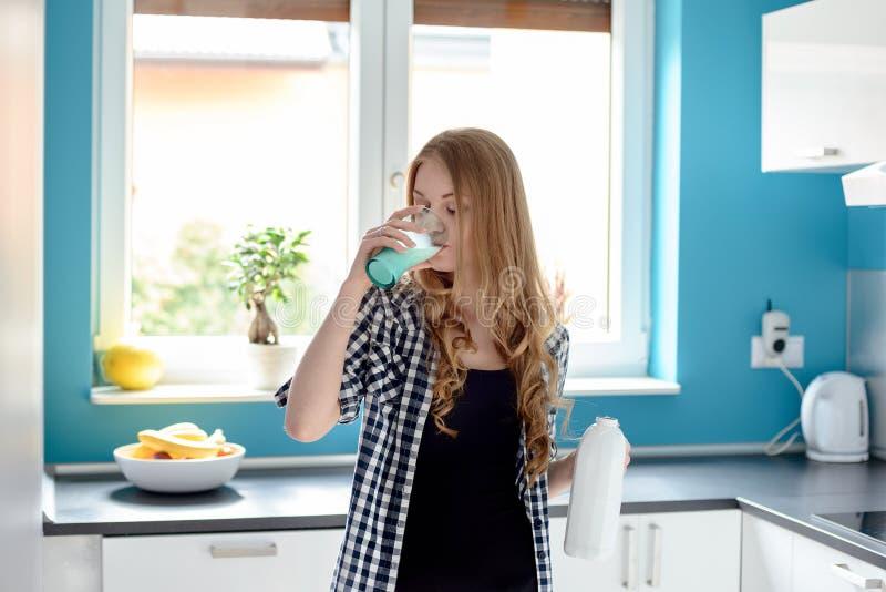Törstigt ungt blont dricka för kvinna mjölkar arkivbild