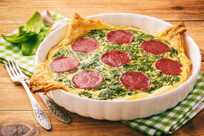 Törtchen mit Spinat und Scheiben der Salami auf hölzernem Hintergrund stockbilder