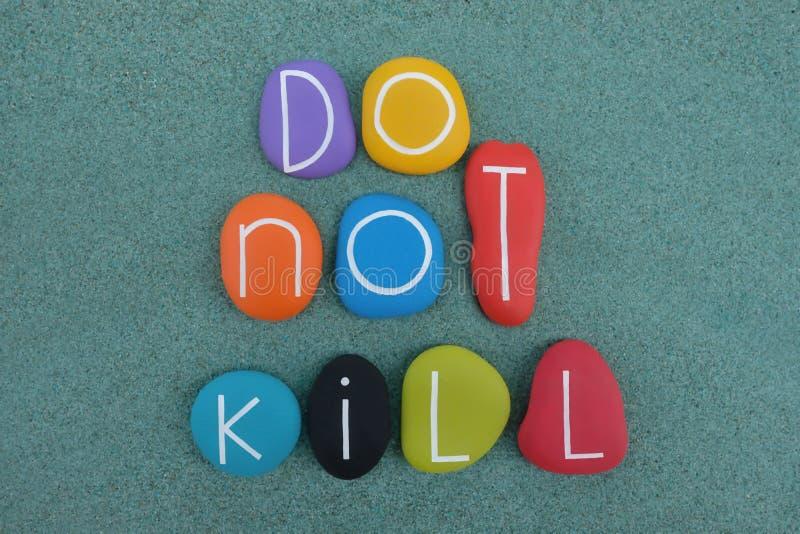 Töten Sie nicht, die Begriffsphrase, die mit multi farbigen Steinen über grünem Sand verfasst wird lizenzfreies stockbild