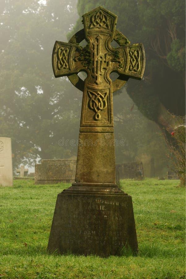 Túmulo antigo no cemitério enevoado na manhã fria fotografia de stock