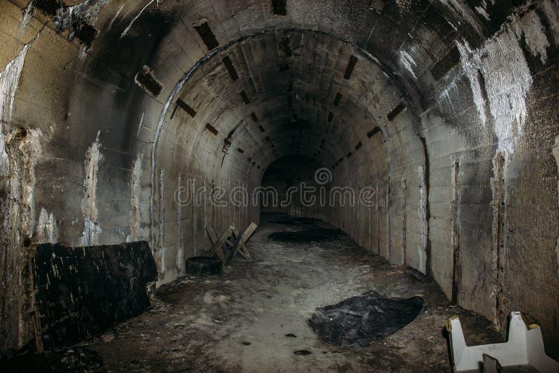 Túnel o pasillo subterráneo largo en arcón o el sótano militar soviética abandonada con la atmósfera espeluznante imagen de archivo
