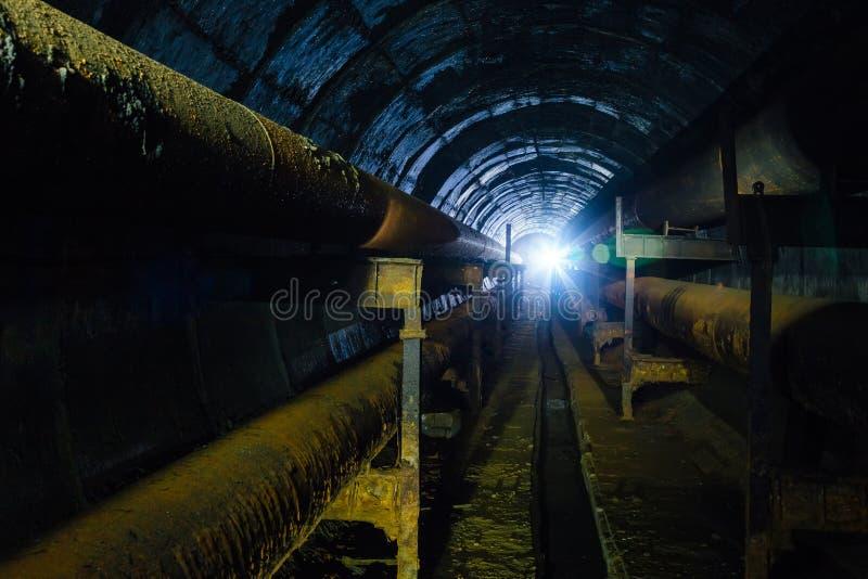Túnel subterráneo concreto redondo del sistema de calefacción del conducto con los tubos oxidados imagen de archivo