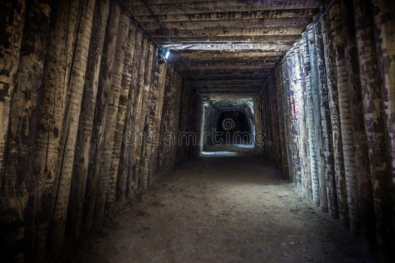 Túnel subterráneo iluminado en mina vieja imagen de archivo