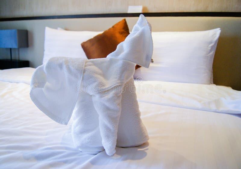 Tücher in Form von Elefanten auf einem bequemen Weiche des weißen Betts Handwerkkünste in den Tuchhotels Babyelefantlappen im Rau stockbild