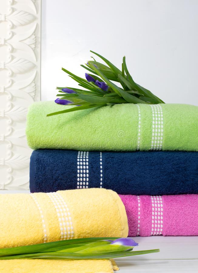 Tücher im Stapel gegen den blured Hintergrund, Stapel grüne, blaue, yelloy und rosa Tücher mit Blumen stockbild