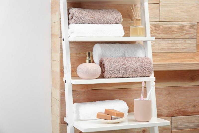 Tücher, Toilettenartikel und Seifenspender auf Regalen stockfoto