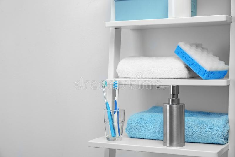 Tücher, Toilettenartikel und Seifenspender auf Regalen im Badezimmer stockfotografie