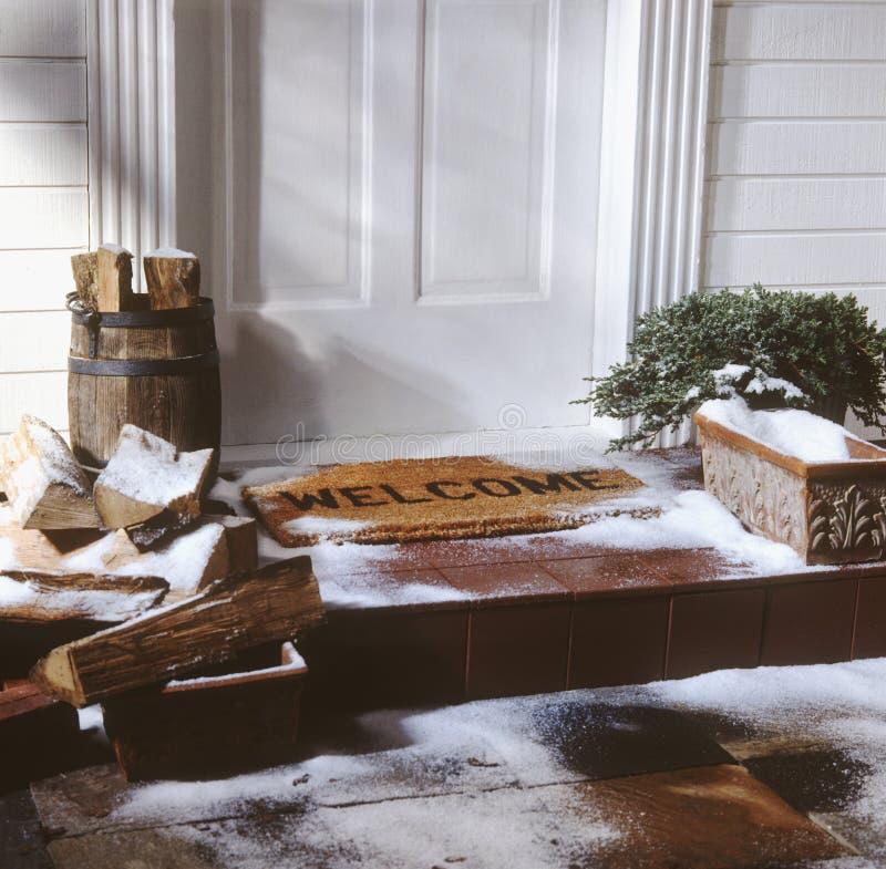 Tür des Hauses mit willkommener Matte im Winter lizenzfreie stockfotos