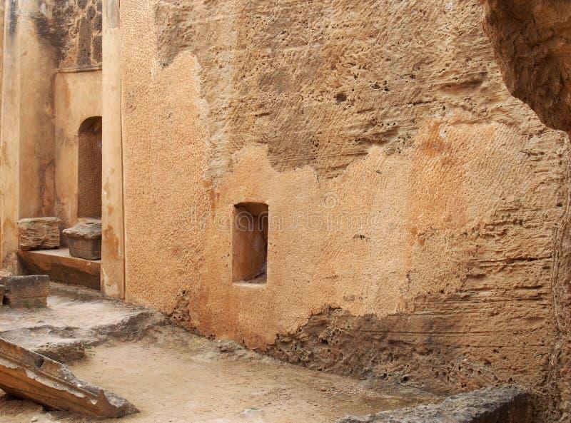 Türen und Nischen in einer geschnitzten Sandsteinwand, die eine Straße wie Ansicht in den Tempel des Königbereichs in den paphos  stockfoto