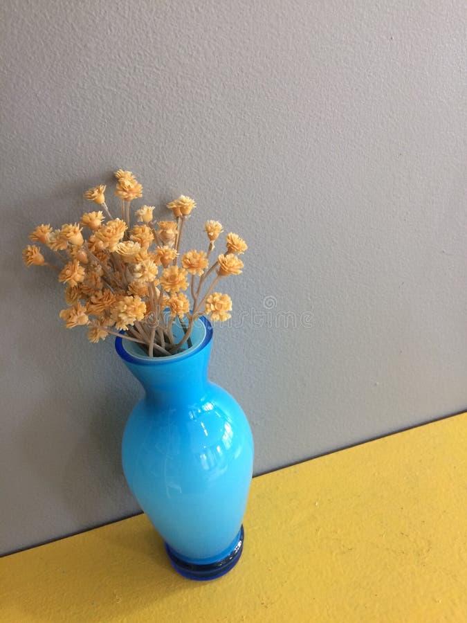 Türkisblaublüht heller Glasknospenvase getrockneten braunen Landblumenstrauß auf gelbem Regal mit grauem Hintergrund lizenzfreie stockfotografie