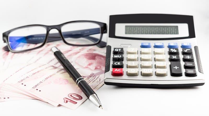 Türkische Banknoten, Gläser, Stift und Taschenrechner auf weißem Hintergrund stockfotografie