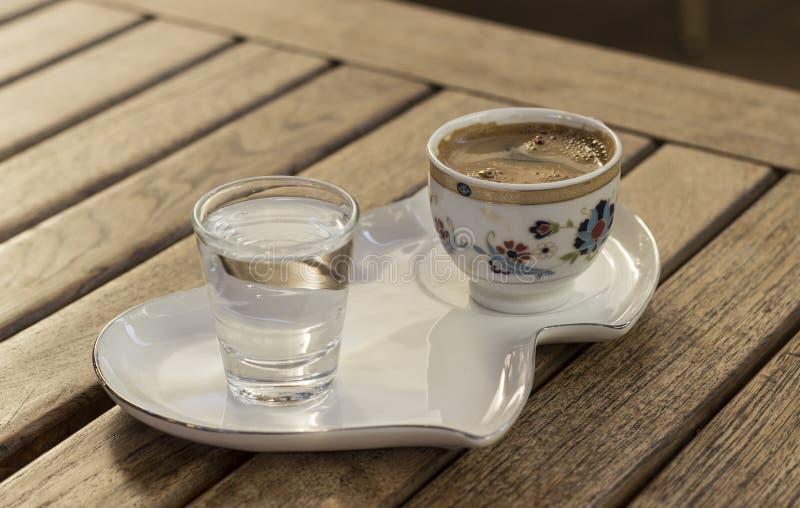 Türkischer Kaffee und Wasser auf einer einfachen Servierplatte lizenzfreie stockfotografie