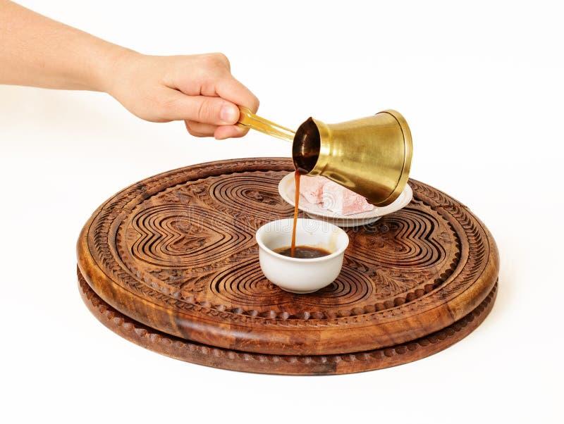Türkischer Kaffee wird in türkische Kaffeetasse gegossen lizenzfreies stockfoto