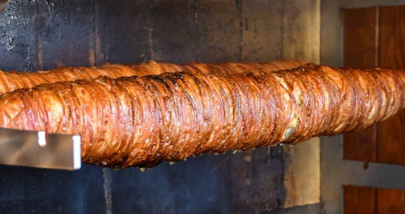 Türkisches Straßen-Lebensmittel Kokorec, das mit dem Schafdarm gemacht wurde, kochte in den Holzofen stockbilder