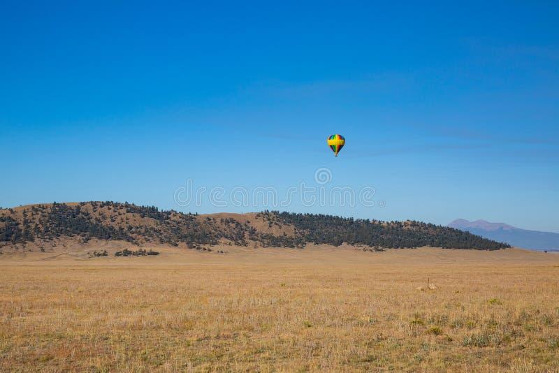 Tęcza barwiący gorącego powietrza ballon unosi się nad dolina i góry zdjęcie stock