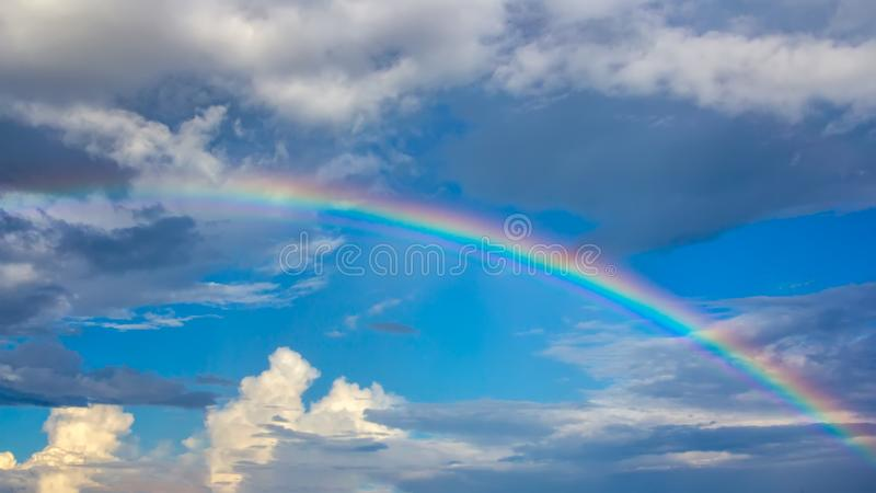 Tęcza nad niebieskim niebem z chmurami obraz stock