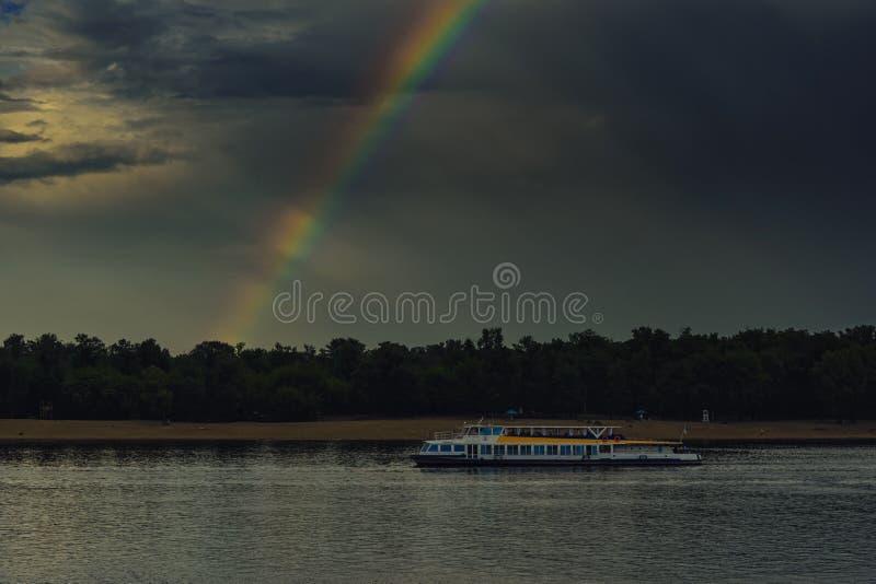 Tęcza od ciemnej chmury nad rzeką i motorowym statkiem zdjęcie royalty free