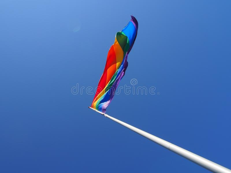 Tęczy flaga przeciw niebieskiemu niebu obrazy stock