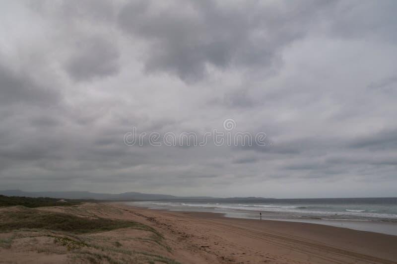 Tęsk piaskowatej plaży linia brzegowa z niskimi burz chmurami obrazy stock