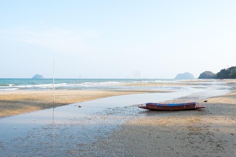 Tęsk plażowy widok na zmierzchu z łodzią rybacką fotografia stock