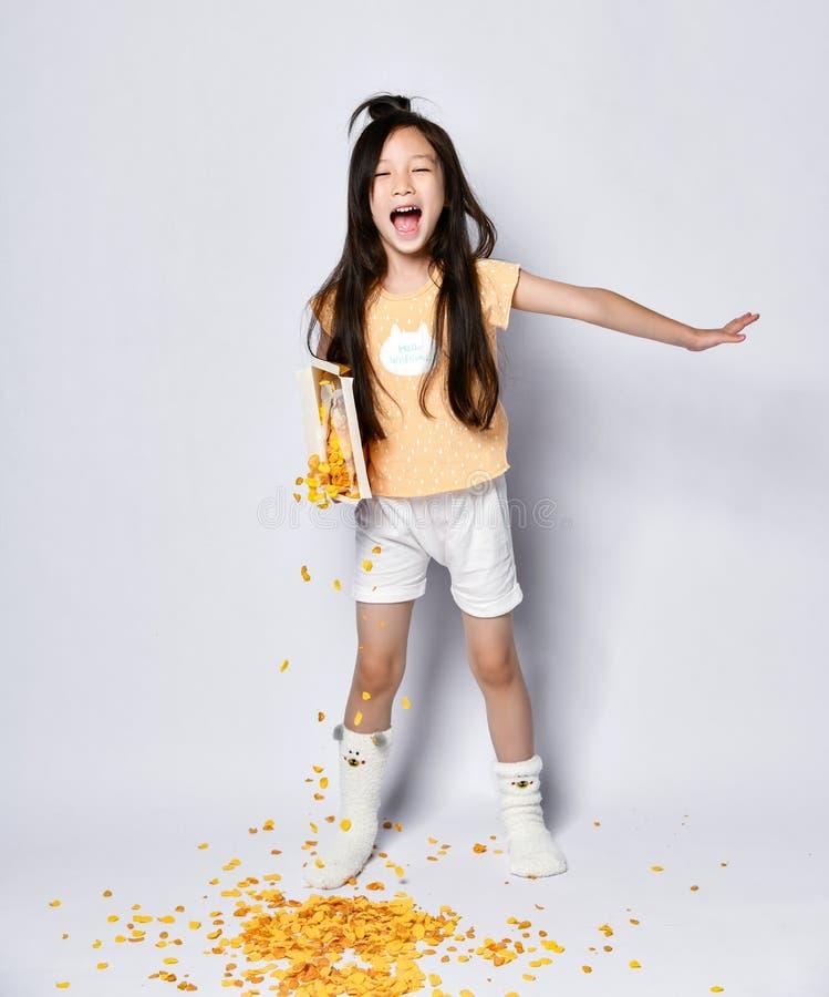 Tęsk z włosami azjatykci dziewczyna dzieciak w domu odzieżowy śpiewacki krzyczeć w ranku śniadaniu i poures za kukurydzanych płat obraz royalty free