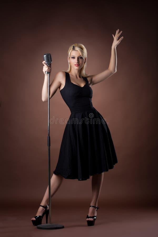 tła śliczna ciemna mikrofonu kobieta zdjęcie stock