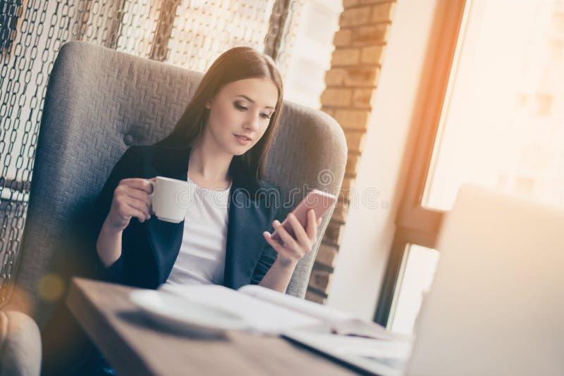 tła śmieszny gwinei lunch nad świniowatym portreta czas biel Poważna młoda biznesowa dama wyszukuje na jej telefonie zdjęcie royalty free