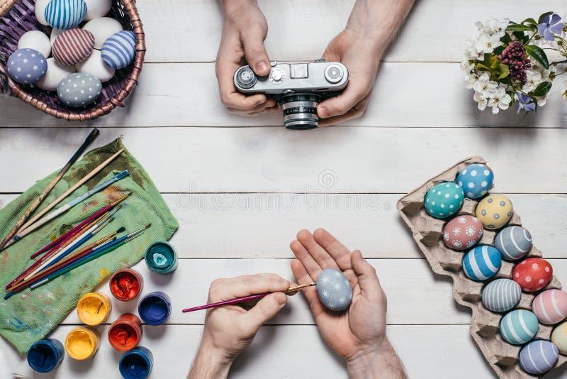 tła chlebowy tortów Easter jajek ciast przygotowanie ocienia miękkiego biel Ludzkie ręki malują Wielkanocnych jajka z muśnięciami obrazy royalty free