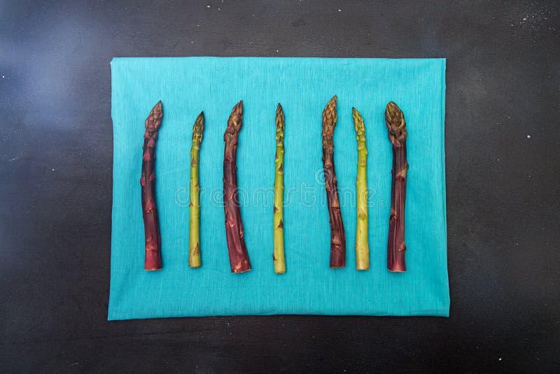 Tła mieszkania nieatutowy zielony purpurowy asparagus na błękicie Ramowy czerń zdjęcie stock