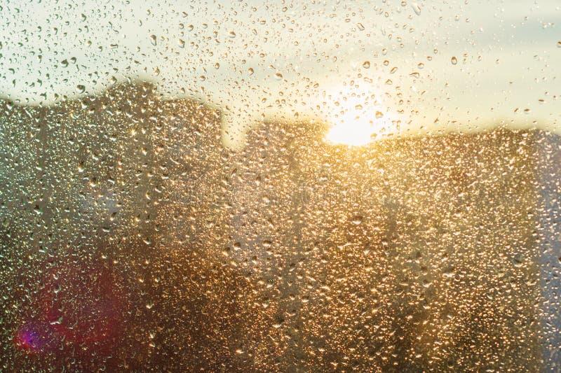 Tła pogodny okno z błyszczącymi podeszczowymi kroplami, widok nowożytny miasto fotografia stock