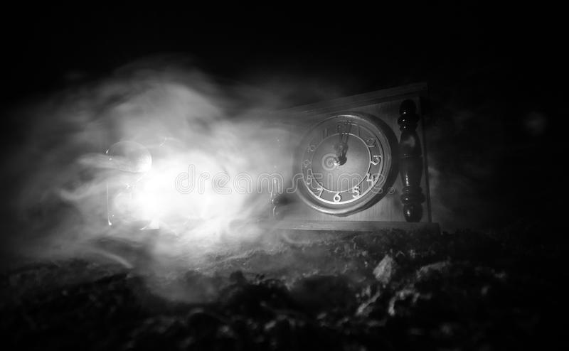 tła pojęcia odosobniony przedmiota czas biel Sylwetka Hourglass rocznika drewna zegar z strzała i dym na ciemnym tle z gorącym żó zdjęcie stock