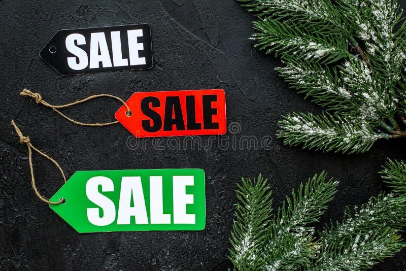 tła sprzedaży teksta wektoru zima Sprzedaży etykietki blisko świerczyny rozgałęziają się na czarnego tła odgórnym widoku obrazy royalty free