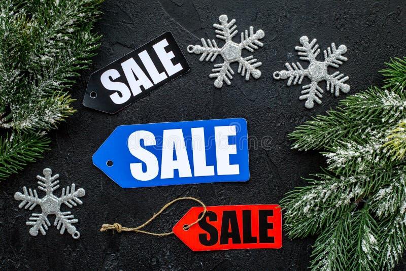 tła sprzedaży teksta wektoru zima Sprzedaży etykietki blisko świerczyny rozgałęziają się na czarnego tła odgórnym widoku zdjęcie stock