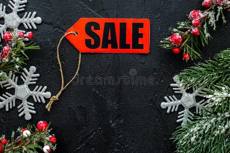 tła sprzedaży teksta wektoru zima Słowo sprzedaż na czerwonej etykietce blisko xmas i świerczyny gałąź na czarnym tło odgórnego w obrazy stock