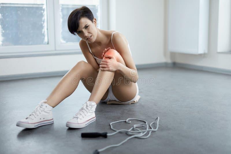 tła uraz odizolowywający nogi biel Piękny kobiety uczucia ból W kolanie, Bolesny kolano fotografia royalty free