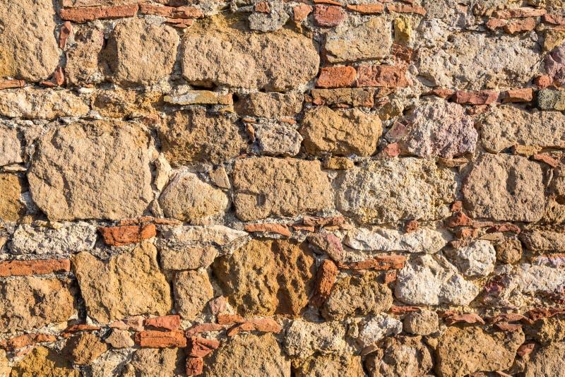 Tło: ściana piaskowiec z włączenie kamieniami i cegłami fotografia royalty free