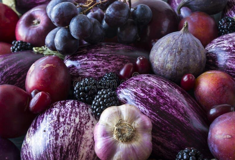 Tło świezi warzywa i owoc Purpurowa oberżyna, czernicy, śliwki, winogrona, figi, jabłka, winogrono i czosnek, Odgórny widok obraz stock