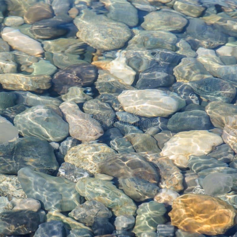 Tło denni barwioni kamienie pod wodą zdjęcie royalty free