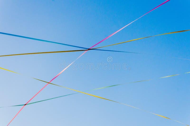 Download Tło Niebieskie Niebo Z Cienkimi Krzyżującymi Barwionymi Faborkami Zdjęcie Stock - Obraz złożonej z dzień, barwiony: 57666556