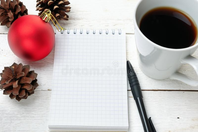 TÅ'o otwartego notesu z pustymi kartkami, obok sosnowych stożków, czerwonej bożonarodzeniowej kuli i filiżanki kawy zdjęcia royalty free