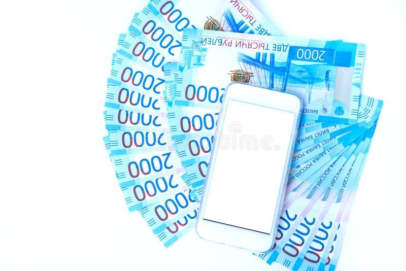Tło pieniędzy banknotów waluty Rosyjski roubleand i telefon komórkowy w nominalnej wartości dwa tysiące Nowy bileta bank Rosja obraz royalty free