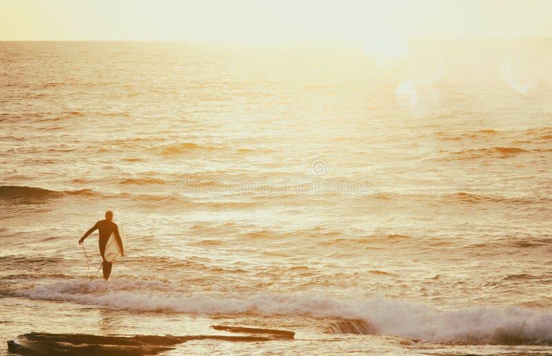 tło plaża, morze i surfingowiec przy zmierzchów kolorami, zdjęcie royalty free