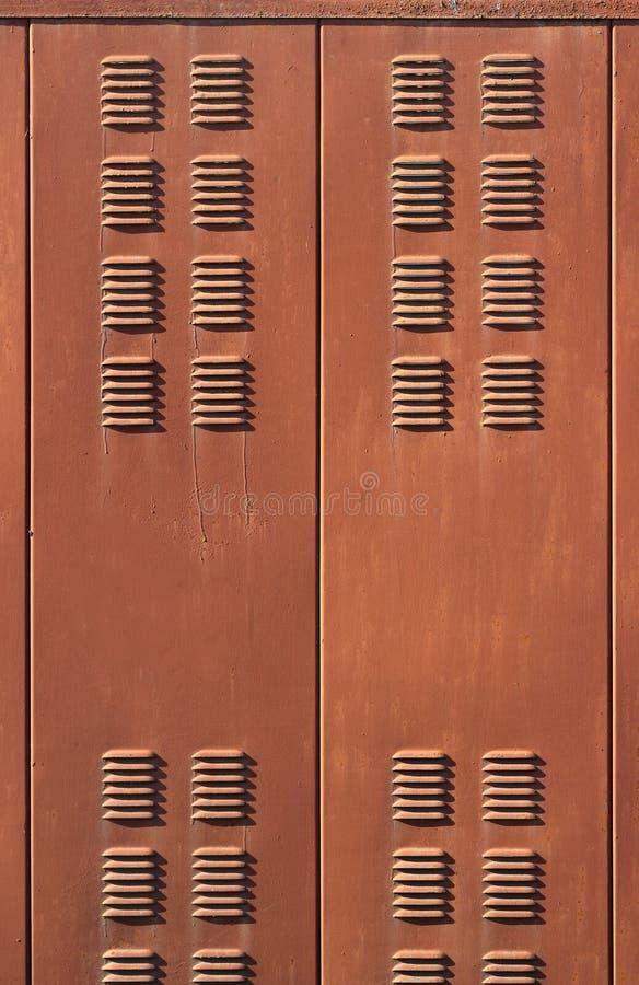 Tło z ośniedziałymi brown metal wentylaci grille drzwiami zdjęcia stock