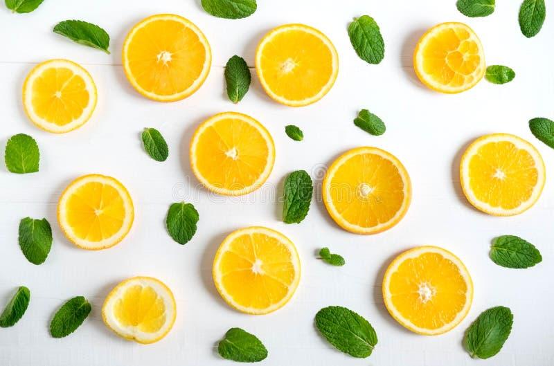 Tło z plasterkami pomarańczowi i nowi liście Jaskrawy cytrusa tło dla sztandaru, strona internetowa Wzór z pomarańczami Widok od fotografia stock