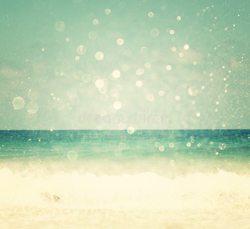 Tło zamazana plaża i morze macha z bokeh światłami, rocznika filtr
