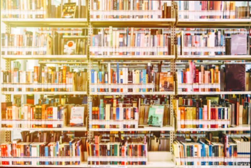 Tło zamazane Obraz wiele książek na półce w bibliotece i pomarańczowy przeciek światła fotografia royalty free