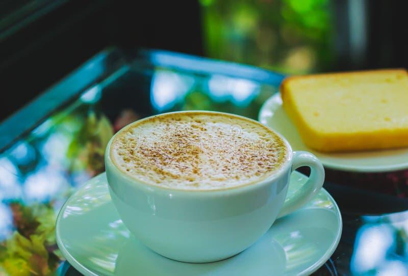 Tło zamazujący mleko spienia w białej filiżance z deserem w tle Na szklanym stole zdjęcia royalty free