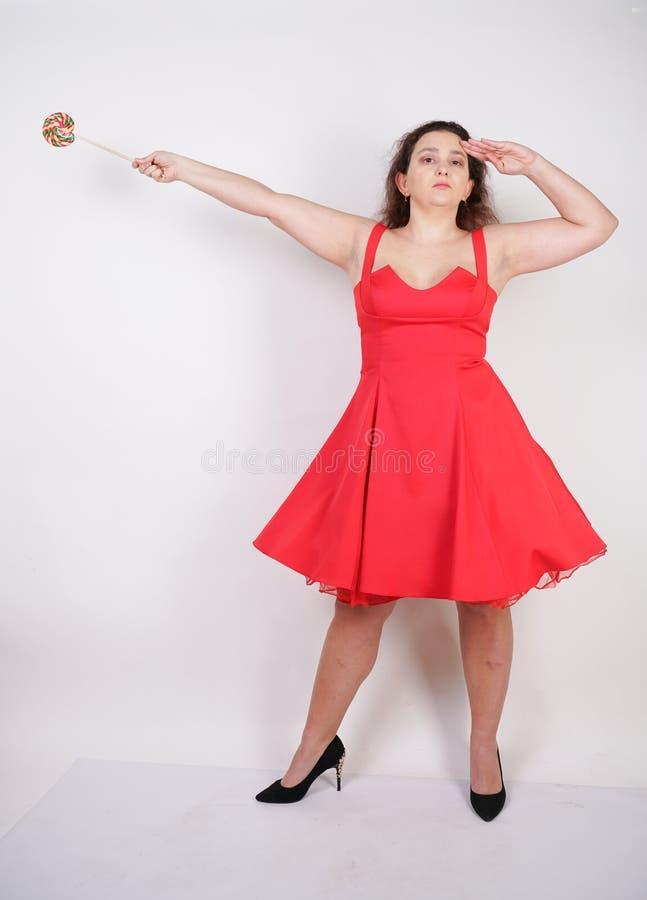 Tłuściuchna kobieta w czerwonej pinup sukni pyzata modna dziewczyny pozycja na białym tle w studiu obraz royalty free