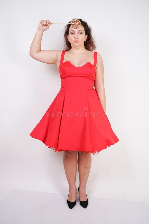 Tłuściuchna kobieta w czerwonej pinup sukni pyzata modna dziewczyny pozycja na białym tle w studiu zdjęcia stock