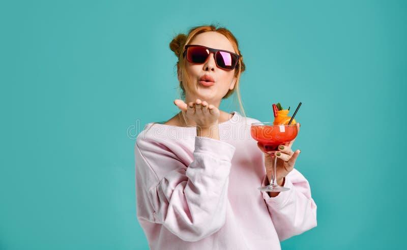 Tłuc młodej nowożytnej kobiety w moda okularach przeciwsłonecznych trzyma zwrotnika koktajl truskawkowy margarita z pomarańczowym zdjęcie stock